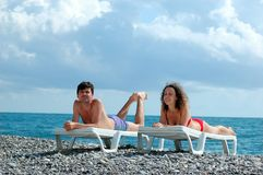 Young man and woman on beach. Young man and woman lies in chaise lounge on beach Royalty Free Stock Photo