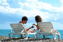 Young man and woman on beach. Young man and woman sit in deckchair on beach Royalty Free Stock Photos
