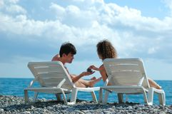 Young man and woman on beach. Young man and woman sit in deckchair on beach Stock Image