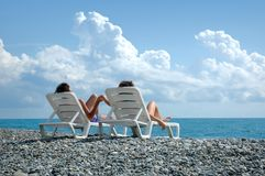 Young man and woman on beach. Young man and woman sit in deckchair on beach Royalty Free Stock Photo