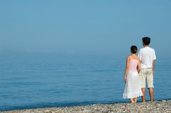 Young man and woman on the beach. Young man and woman standing embraced on the beach Stock Photo