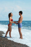 Young man and woman on the beach Royalty Free Stock Image