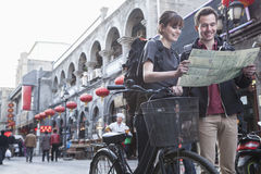 Young man and woman with bicycle and map. Royalty Free Stock Image