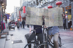 Young man and woman on bicycles holding maps. Royalty Free Stock Photography