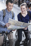Young man and woman on bicycles, looking at map. Stock Photos