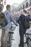 Young man and woman with bicycles, walking down street. Stock Photos