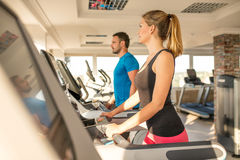 Young man and woman biking in the gym, exercising legs doing car Royalty Free Stock Photography