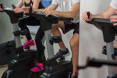Young man and woman biking in the gym, exercising legs doing cardio workout cycling bikes Royalty Free Stock Photos