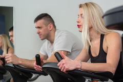 Young man and woman biking in the gym, exercising legs doing cardio workout cycling bikes. Young men and women biking in the gym, exercising legs doing cardio Royalty Free Stock Photography