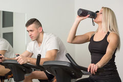 Young man and woman biking in the gym, exercising legs doing cardio workout cycling bikes Stock Photography
