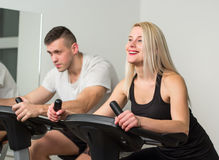 Young man and woman biking in the gym, exercising legs doing cardio workout cycling bikes Stock Images