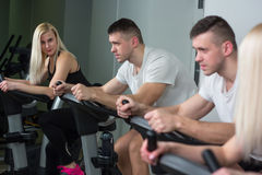 Young man and woman biking in the gym, exercising legs doing cardio workout cycling bikes Stock Photos