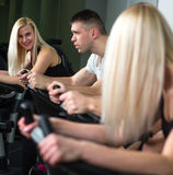 Young man and woman biking in the gym, exercising legs doing cardio workout cycling bikes Royalty Free Stock Photo