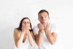 Young man and woman blowing confetti decorations Stock Image