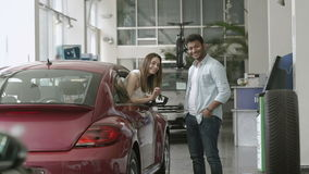 Young man and woman bought a car in car showroom. Happy swarthy guy looks on girl in car and smiling. Pretty girl appears from car`s window and demonstrate the stock video footage