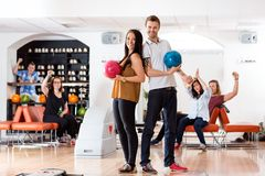 Young Man And Woman With Bowling Balls in Club Stock Photo