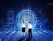 Young man and woman businessmen stand and look at hologram of big data against the background of the night city with skyscrapers stock photography
