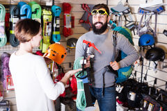 Young man and woman buying alpinism equipment royalty free stock photography