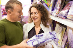 Young man and woman buying bedding in supermarket. Smiling young man and woman buying bedding in supermarket, looking each other Royalty Free Stock Photos