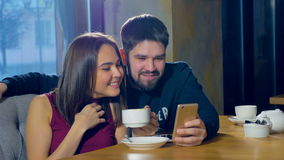 Young man and woman in cafe using new application on smart phone. Smiling happy, casual teens. stock video