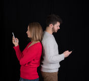 Young man and woman with cellphones Stock Image