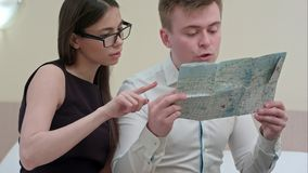 Young man and woman checking map, talking, planning family vacation royalty free stock photo