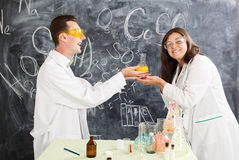 Young man and woman in a chemistry lab created an elixir. Couple chemists enjoy of chemistry experiment. Young men and women in a chemistry lab created an stock image