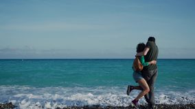 Young man and woman come to the shore of the azure sea and cuddle. Sea wave suddenly rushes and wet their feet. Lovers. Laugh and wonder at what happened 4k stock video footage