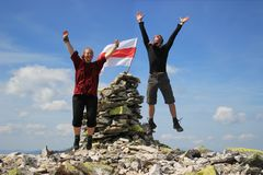 Young man and woman couple jumping for joy at the top of a mountain with a flag royalty free stock photo
