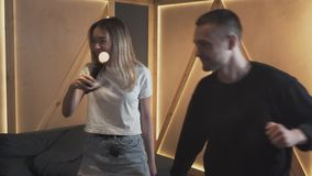 Young man and woman dancing in the loft style room holding luminous motion sensors and smiling. Happy couple spending. Young happy man and woman dancing in the stock video