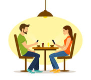 Young man and woman on a date in cafe with smartphones Royalty Free Stock Image