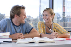 Young man and woman at desk studying, smiling at each other, close-up Stock Image