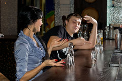Young man and woman disputing the last drink. Young men and women disputing the last drink of vodka in the bar with the women gesticulating and the men pointing stock image