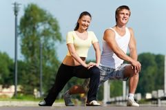 Young man and woman doing. Young fitness couple of man and woman doing physical stretching exercises before jogging sport outdoors Royalty Free Stock Image