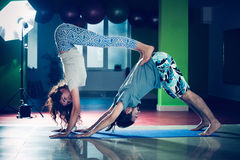 Young man and woman doing acro yoga  indoor Stock Photos