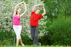 Young man and woman doing stretching exercises Stock Photos