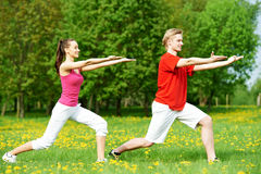 Young man and woman doing stretching exercises. Young fitness men and women doing physical stretching exercises during outdoors sport training Stock Images