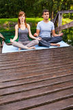 Young man and woman doing yoga in garden Royalty Free Stock Photo