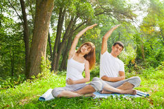 Young man and woman doing yoga in garden Royalty Free Stock Photography