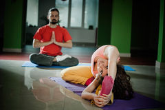 Young man and woman doing yoga  indoor Royalty Free Stock Images