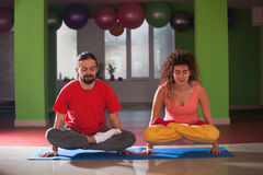 Young man and woman doing yoga  indoor Royalty Free Stock Photo