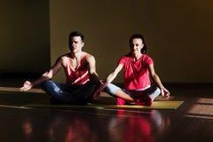 Young man and woman doing yoga. Lotus pose meditation Stock Images