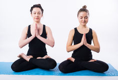 Young man and woman doing yoga and meditating in lotus position  on white background. Royalty Free Stock Photo