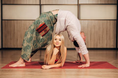 Young man and woman doing yoga in pair stock photography