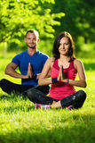 Young man and woman doing yoga in the sunny summer Stock Photography