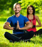 Young man and woman doing yoga in the sunny summer Royalty Free Stock Photos