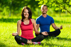Young man and woman doing yoga in the sunny summer park Stock Image