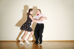 Young man and woman in dress dance at boogie-woogie party. Young happy men and women in dress dance at boogie-woogie party Stock Images