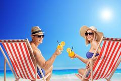 Young man and woman drinking cocktails at a beach. Young men and women sitting on sun loungers and holding cocktails at a sunny beach stock image