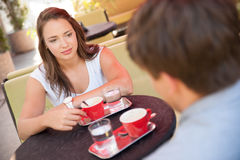 Young man and woman drinking coffee outdoor and having a chat on stock photo